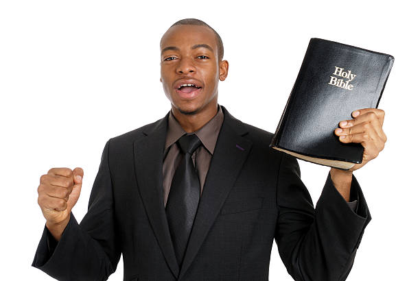 man holding a bible preaching the gospel - preacher stock photos and pictures