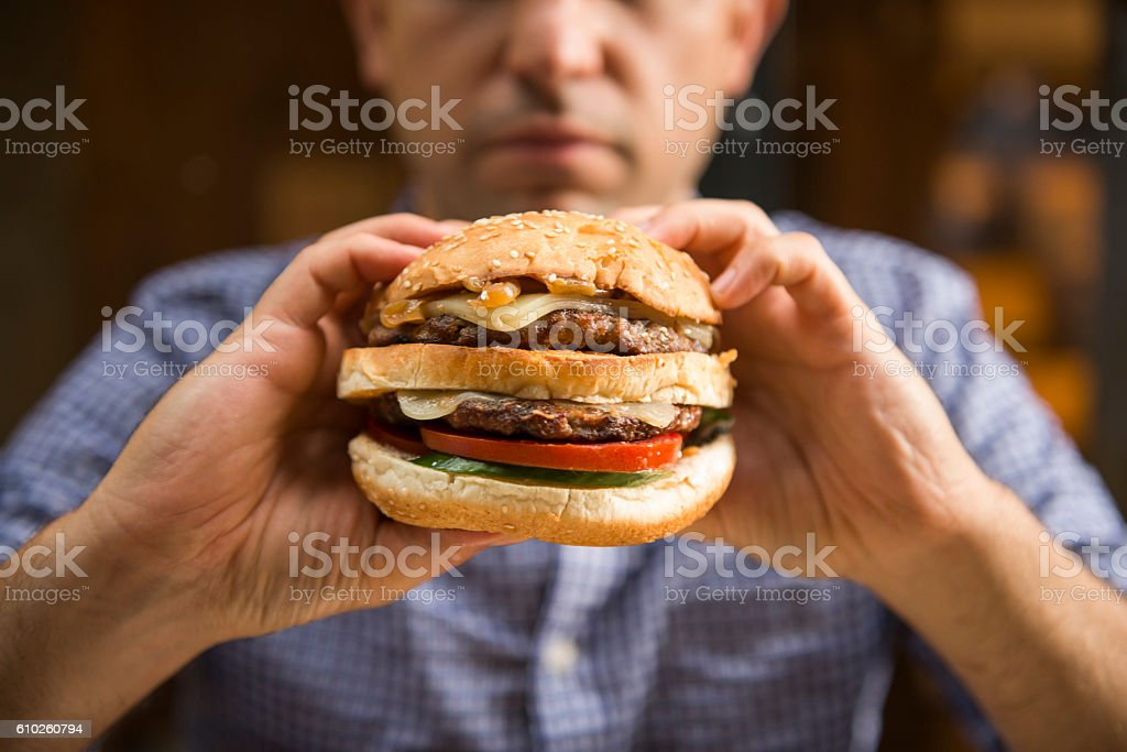 Man holding a big hamburger stock photo