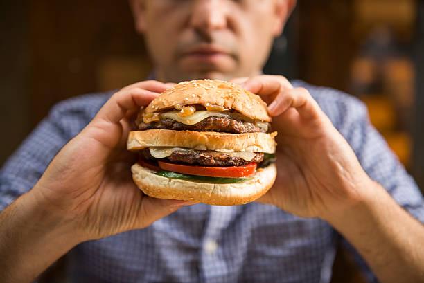 Man holding a big hamburger stock photo