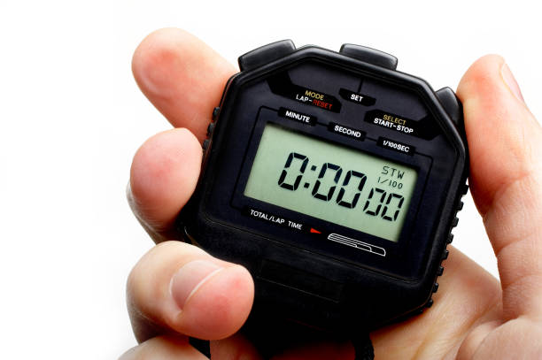 Man holding a black digital stopwatch set to zero stock photo