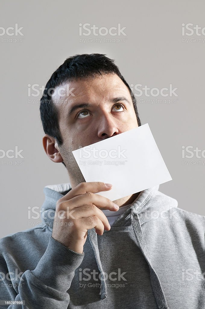 Man holding a blank card in front of his face royalty-free stock photo