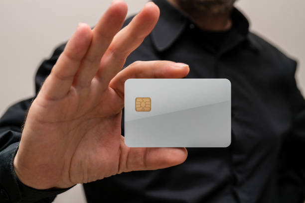 man holding a blank credit card in hands - gift voucher or card stock photos and pictures