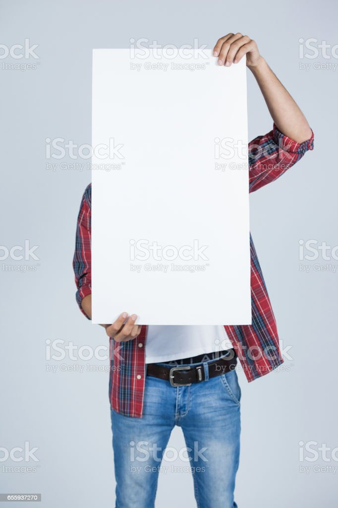 Man holding a blank placard in front of his face stock photo