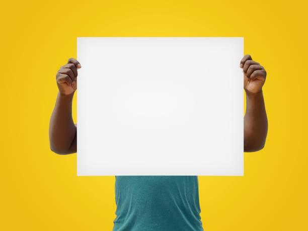 man met een blanco wit teken op een gele achtergrond - verduisterd gezicht stockfoto's en -beelden