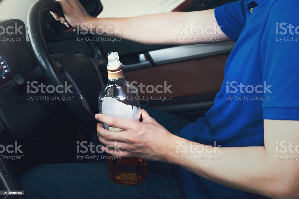 Man holding a bottle of liquor while driving stock photo