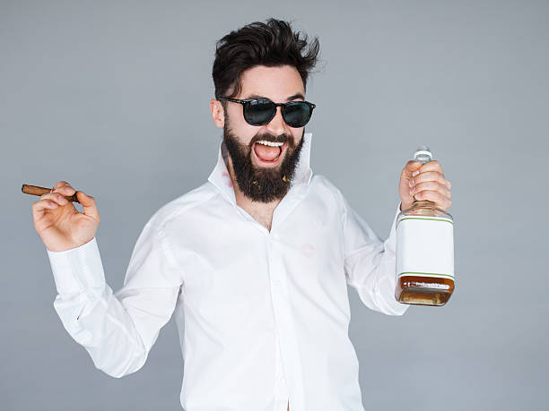 man holding a bottle of whiskey and cigar stock photo