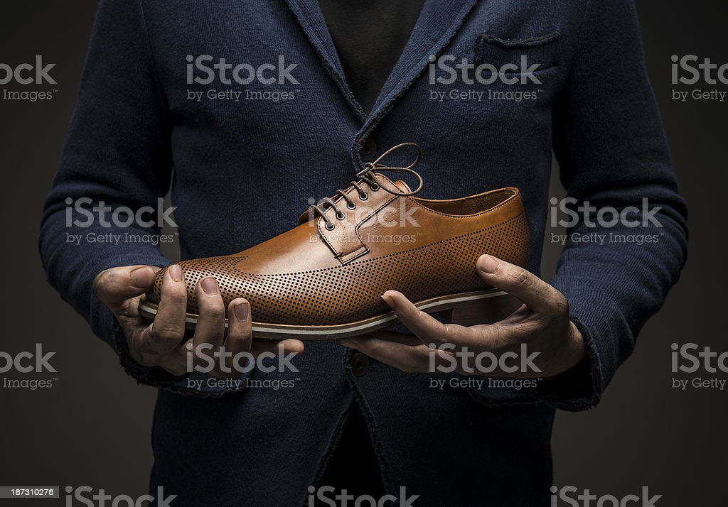 Man holding a brown leather shoe stock photo