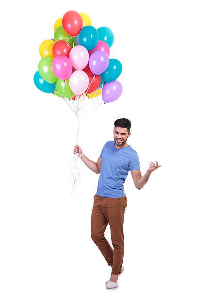 mann hält einen haufen bunte ballons ist einladend party - ballonhose stock-fotos und bilder