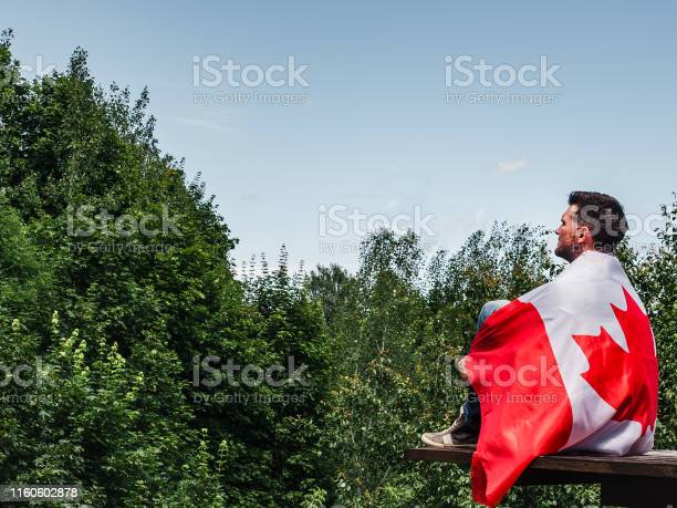 Photo of Man holding a Canadian Flag. National holiday