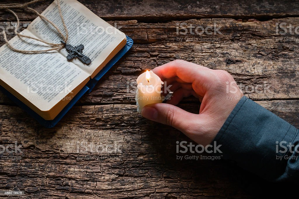man holding a candle of the bible and cross man holding a candle in front of the bible and cross selective focus 2015 Stock Photo