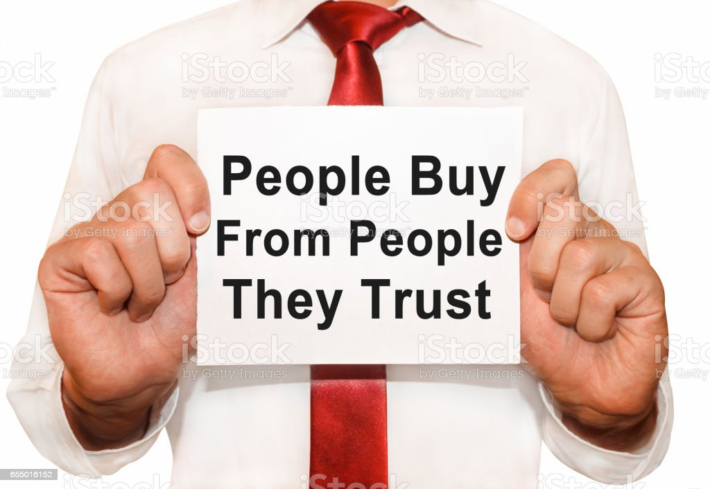Man holding a card with a text People Buy From People They Trust. stock photo
