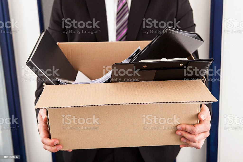 A man holding a cardboard box with work supplies in it stock photo