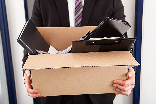A man holding a cardboard box with work supplies in it Portrait of young businessman holding cardboard in office downsizing unemployment stock pictures, royalty-free photos & images