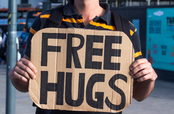 Man holding a cardboard sign with free hugs written on it stock photo