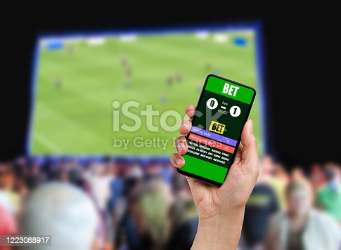 Close-up on man holding a cell phone while winning an online bet on a football game at bar.