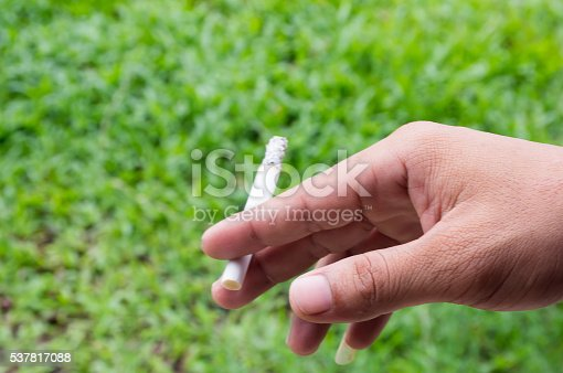 man holding a cigarette and a smoke and blur green grass background