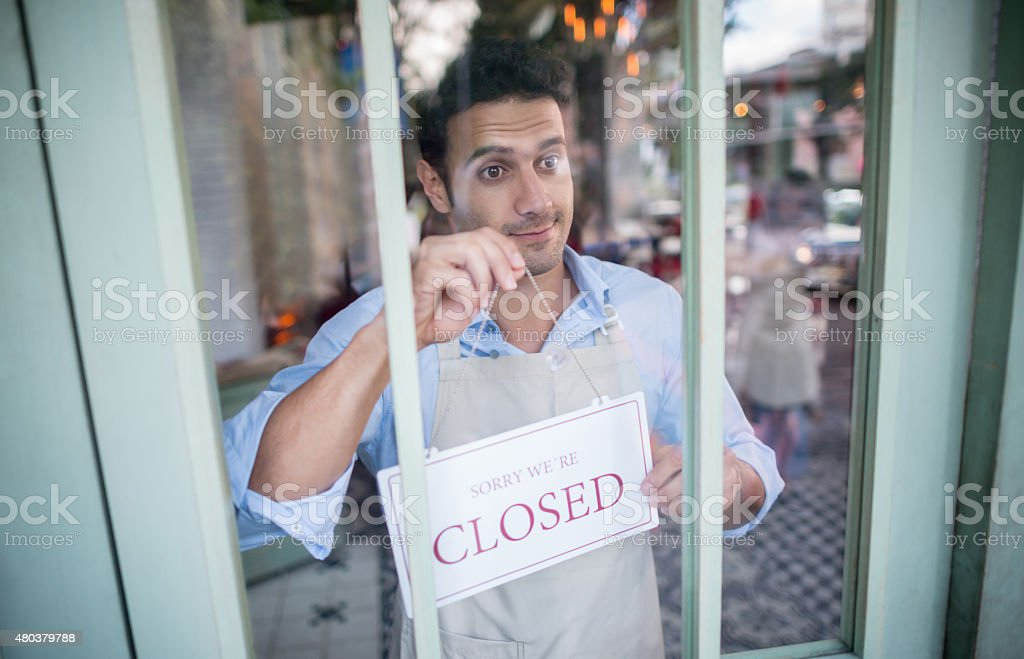 Man holding a closed sign outfront of his business stock photo
