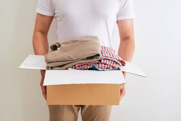 Man holding a clothes donate box. Donation concept. stock photo