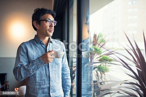 istock Man holding a coffee cup looking through window 540509572