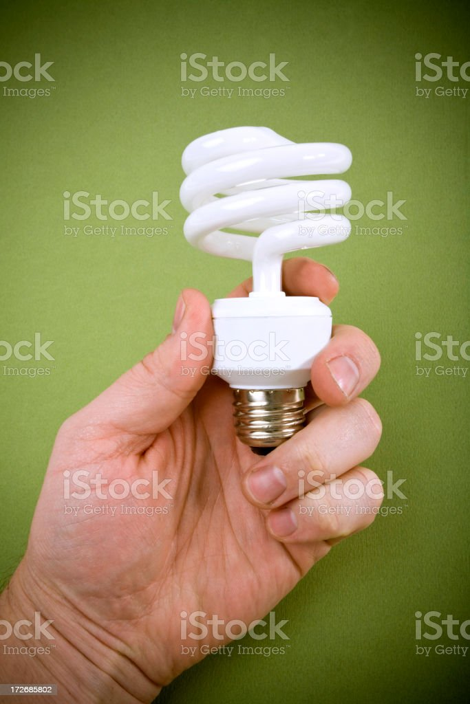 Man Holding a Compact Fluorescent Light Bulb royalty-free stock photo
