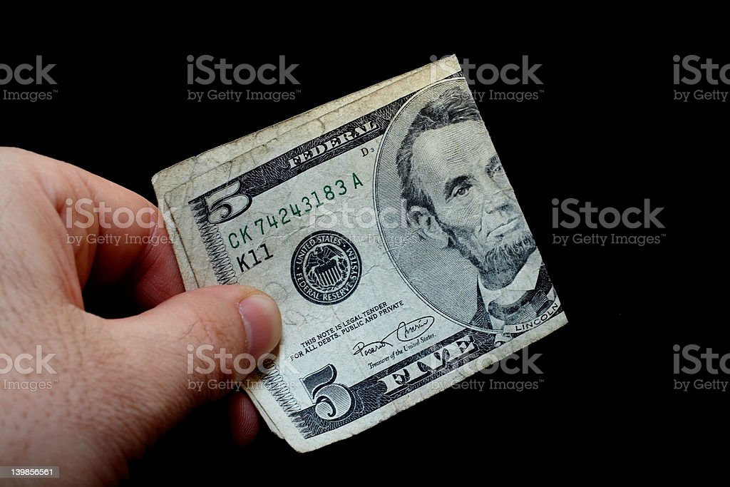 Man holding a five dollar bill royalty-free stock photo