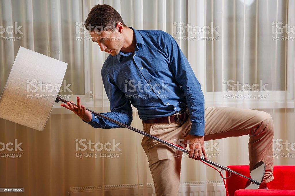 Man holding a floor lamp royaltyfri bildbanksbilder