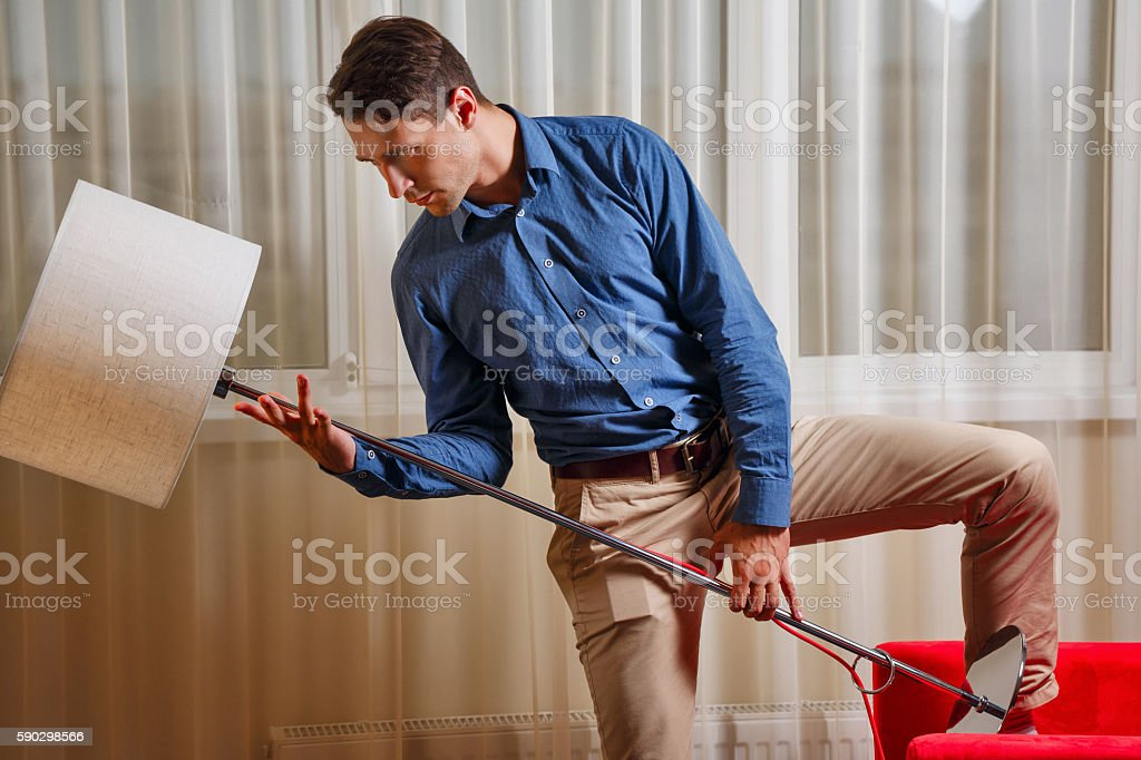 Man holding a floor lamp stock photo