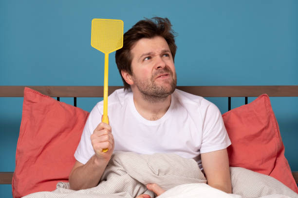 man holding a fly swatter wanting to kill annoying mosquito stock photo