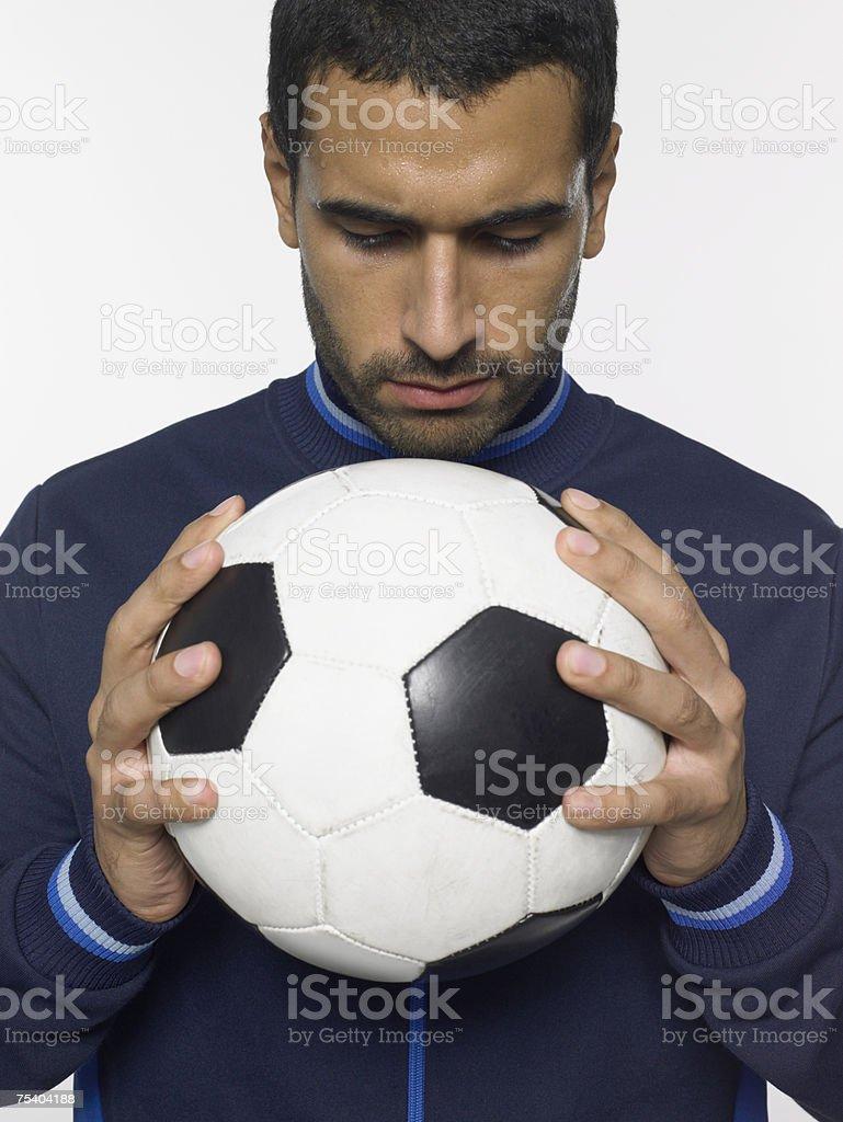 Homem segurando uma bola de futebol foto de stock royalty-free