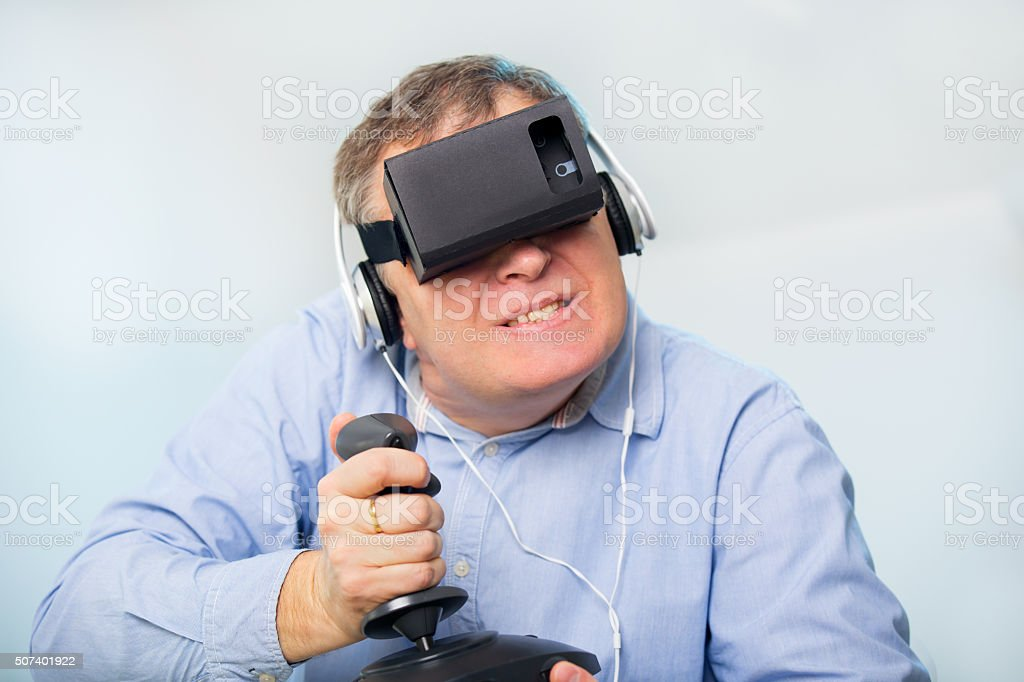 f88132c080a Man holding a gaming computer wheel getting experience using VR-headset  royalty-free stock