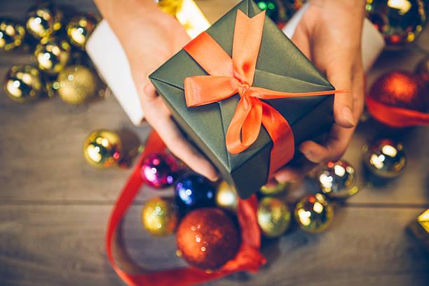 man holding a gift box in a gesture of giving - weihnachtsideen stock-fotos und bilder