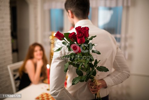 istock Man holding a gift for his girlfriend 1126891725