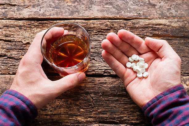 man holding a glass of alcohol and pills - sleeping pill stock photos and pictures