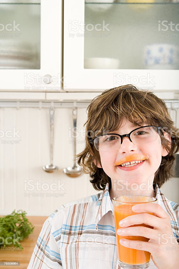 A man holding a glass of carrot juice 免版稅 stock photo
