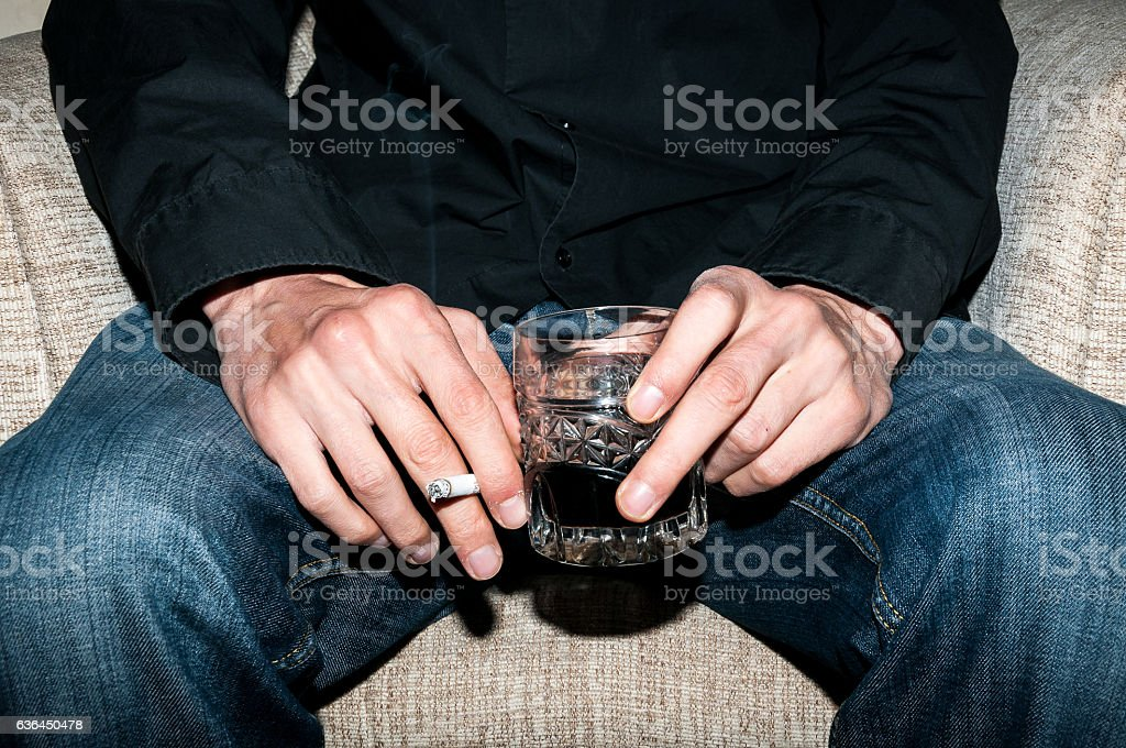 Man holding a glass of whiskey and smoking a cigarette. stock photo