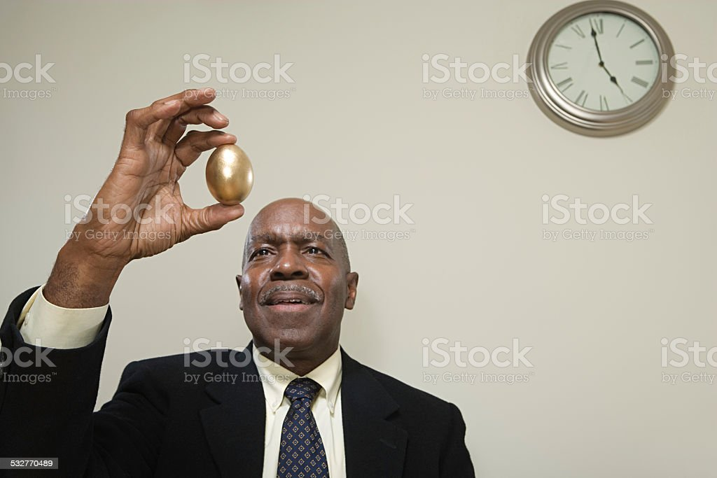 Man holding a golden egg stock photo