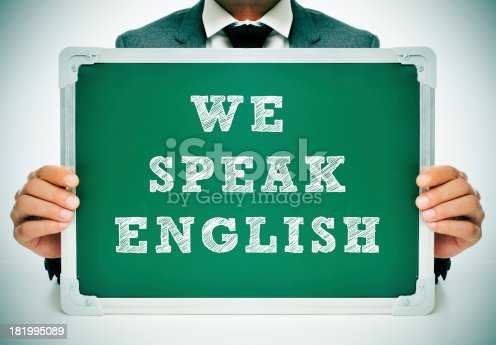 istock Man holding a green sign that says We speak English 181995089