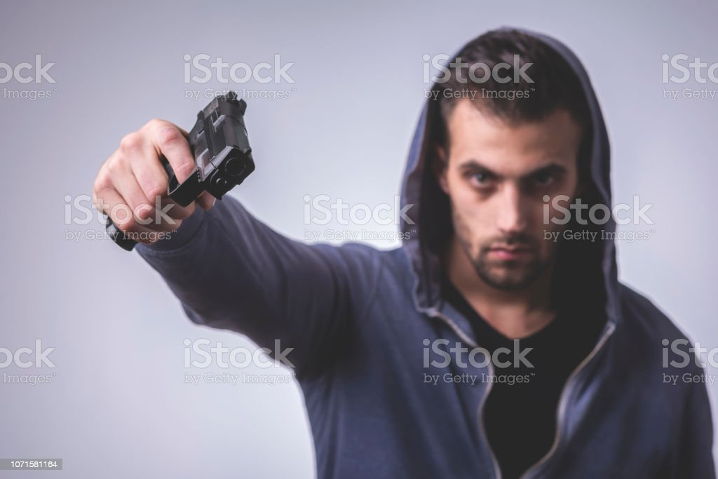 A man holding a gun in hand, the ship ready to shoot the man pointed....
