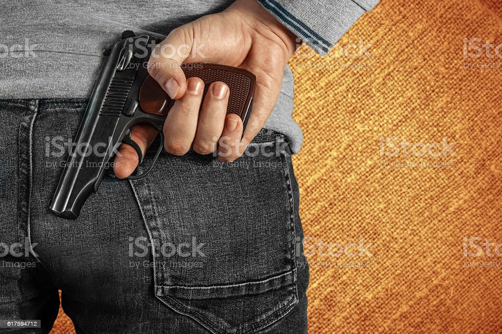 Man holding a gun in his hand behind his back stock photo