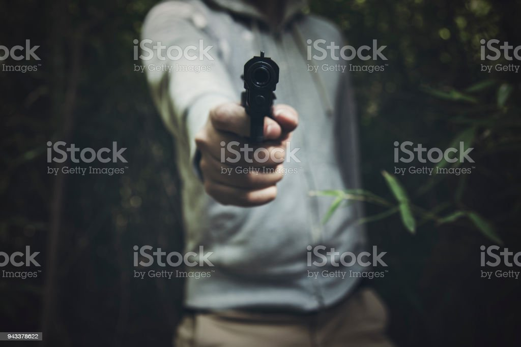 Man holding a gun in the bush stock photo