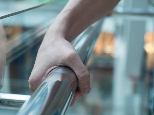 man houdt een hand rail in winkelcentrum close-up - veiligheidshek stockfoto's en -beelden
