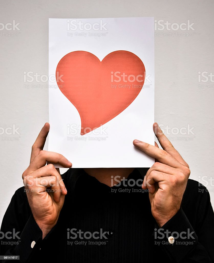 Man holding a heart hiding the face royalty-free stock photo