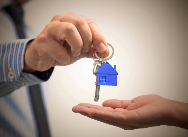 man holding a home key in his hand stock photo