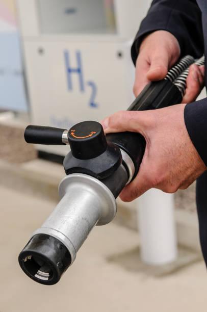 Mann mit Wasserstoff-Tankerdüse zum Betanken von wasserstoffbetriebenen Fahrzeugen – Foto