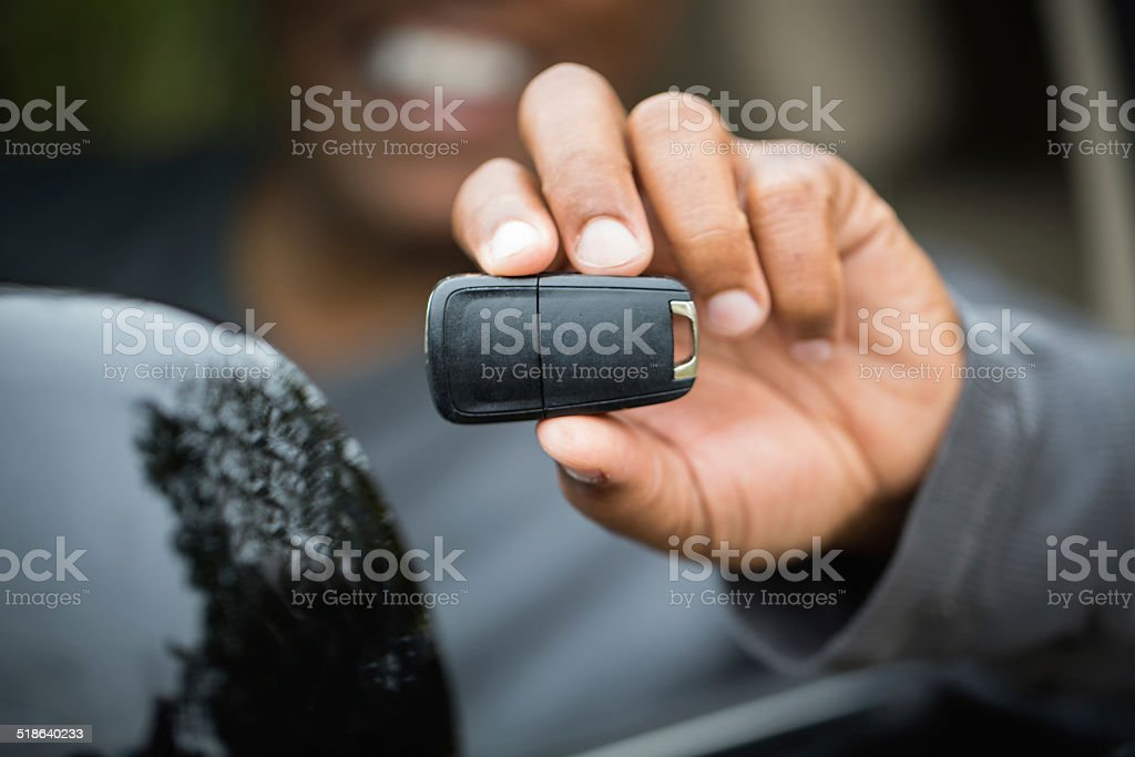 Man holding a key to a new car stock photo
