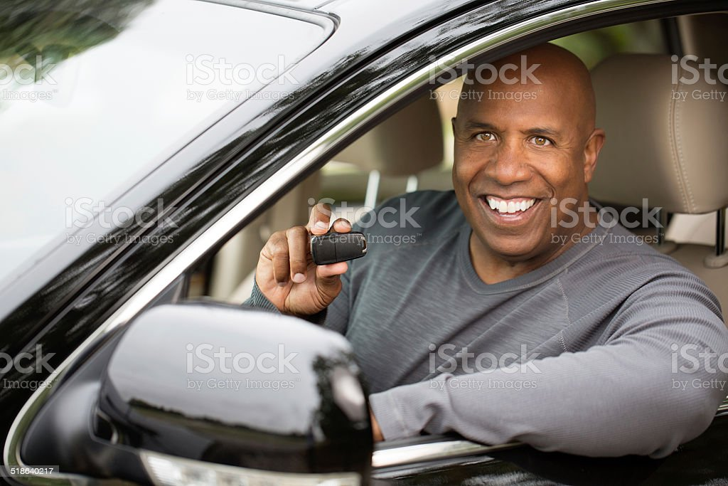 Man holding a key to his new car stock photo