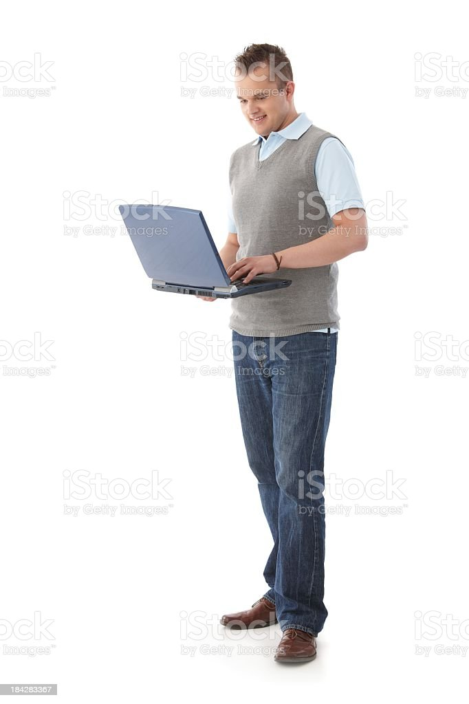Man holding a laptop in one hand and pressing keys royalty-free stock photo
