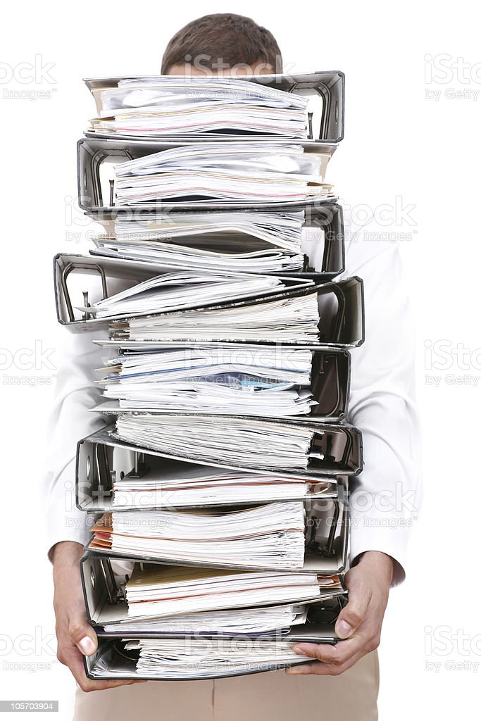 A man holding a large pile of binders filled with papers. stock photo