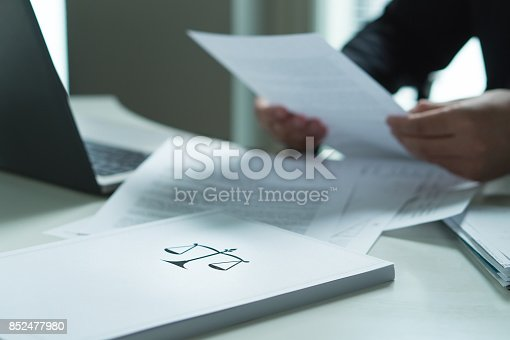 istock Man holding a legal document in hand. Lawyer holding law paper in office. Scale and justice symbol. 852477980