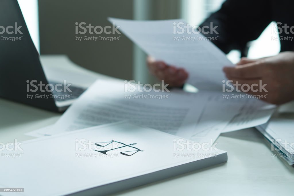 Man holding a legal document in hand. Lawyer holding law paper in office. Scale and justice symbol. stock photo